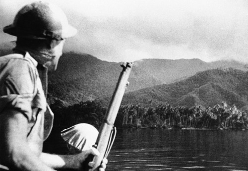 A helmeted Australian soldier overlooking New Guinea
