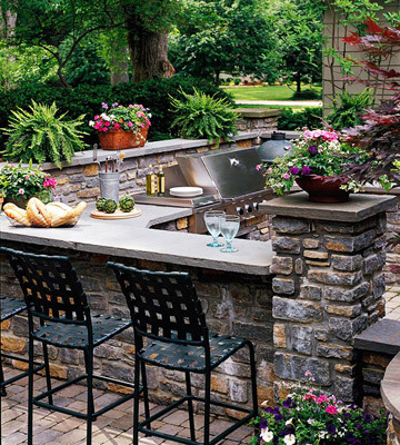 An outdoor kitchen with stone walls, a grilling station, and casual bar-style seating (via Outdoor Rooms to Live in All Summer Slide Show)