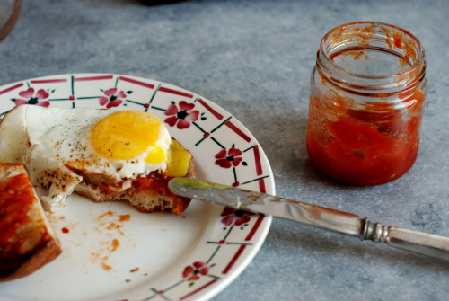 Tomato jam is a funny thing; sweet when you're expecting salty, savory  when you're expecting sweet. I spread it on a piece of crusty bread and  topped it with a fried egg, the gooey yolk sort of swimming into the  hot, sweet jam.