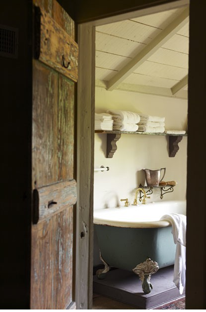 Great rustic farmhouse bathroom with an old solid wood plank door, sloped wood ceiling, and claw foot bathtub (via .nest. / bath)