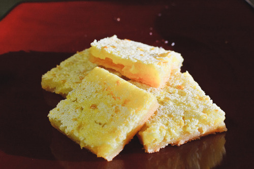 Do you know how easy making lemon bars is? The answer is incredibly easy, as long as you don't have any cuts on your hands, because lemon zest in cuts… it stings and will make squeezing lemons a lot slower. Now, I love lemon bars, who doesn't? And these are the best, the crust is good the lemon is sweet and zesty. I've made this recipe a bunch for parties. I used a recipe from the blog In Erika's Kitchen, this recipe is almost the same, I just added lemon zest for a bit of a tarter taste. If you decide to make this for a party I suggest you double or triple the recipe.  Lemon Bars   1 1/8 cups   all-purpose flour divided 1/2 cup   powdered sugar (and an extra 2 tablespoons to shake over the bars) 1/2 cup (1 stick)   butter, melted  Pinch of   salt  2   eggs  1 cup   granulated sugar  1/2 tsp   baking powder  1/3 cup   fresh lemon juice (about 2-3 lemons) 1 Tbs lemon zest (or to taste)Preheat  the oven to 350 degrees. Spray a 9x9-inch pan with baking spray or line the pan with parchment paper. In   a bowl, mix together 1 cup of the flour, 1/2 cup of the powdered  sugar,  the melted butter, and the salt with a fork until a crumbly  dough  forms. Press the dough into the prepared pan so it covers the  bottom and  goes about 1/2 inch up the sides. Bake the crust about 15  minutes or  until it just starts to turn golden.   While   the crust is baking, whisk together the remaining 1/8 cup flour, eggs,   granulated sugar, baking powder and lemon zest and juice.  Quick note on lemon zest: the zest is the skin, but NOT the white part. Let me repeat that: YOU DO NOT WANT THE WHITE PART (also known as the pith), THE WHITE PART IS BITTER. Bitter is bad, tart is good. There's a difference, trust me on this. So when you go to grate the lemon zest (use a fine grater) stop when you see white. If you get a little of the pith in your zesting quest, don't worry, you just don't want a lot. Pull the crust out of  the oven, pour over the lemon mixture, and return  the pan to the oven  for another 30 minutes, or until the center no  longer jiggles when you  shake the pan. Cool   the lemon bars in the pan for half an hour, then refrigerate at least   two hours before cutting. Cut with a large knife  into 9 even squares,  like a tic-tac-toe board. Dust the lemon bars with  the 2 Tbsp powdered  sugar before serving. Total time: 55 mins (with refrigeration 3 hours)(Picture taken by Eddie Barksdale)