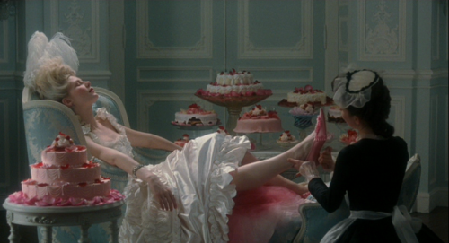 Marie Antoinette (2006)  This, my friends, is the very first shot in the movie. Love her or hate her, Sofia Coppola has a masterful understanding of the importance of cake in cinema. Gender issues, class issues, ominous foreshadowing — it's all here from frame one.  Thanks to Coppola we see that Marie's life is devoid of any profound personal attachments, so to keep from losing her mind, she channels her love and devotion into utterly trivial, superficial things. Shoes, candy, mansions — for a person to whom money means nothing, all pleasures are interchangeable, there is no standard by which one qualifies them except one's own delight. Meanwhile, she herself is a fetish object. Her value is determined by her appearance, her rank, and her fertility. As a sweet, decorative and ultimately disposable bauble, she becomes cake incarnate.  It's only fitting that such a person would become forever (erroneously) associated with the pastry. Coppola grants our heroine a reprieve, allowing us to glimpse her reaction to the famous line as it is reported in the newspaper. By the end of the film Marie seems to be on the verge of developing a taste for reality, looking beyond the pink-frosted castle walls to see what life is like for the 99% outside. But it's too little, too late, and Marie is taken away from us before we ever learn whether she can truly be rehabilitated.