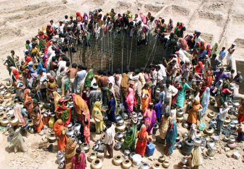 olio-ataxia:  People gather to get water from a huge well in the village of Natwarghad in the western Indian state of Gujarat on June 1, 2003. (Reuters/Amit Dave) #img 32