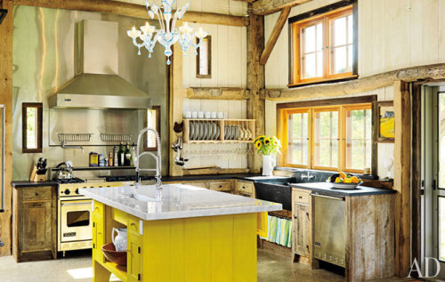 Obsessed with this kitchen and the yellow island.   In a 200-year-old barn that she transported to coastal Rhode Island,  designer Ellen Denisevich-Grickis created an eclectic kitchen setting:  Rustic beams mix with a vibrant Shaker-style island, Murano-glass  chandelier, and Viking stainless-steel appliances. The concrete floors  are embedded with chips of mirror, mother-of-pearl, abalone shell, and  sea glass.