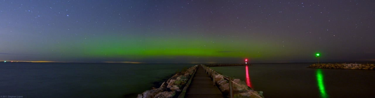 "Aurora Borealis over Lake Ontario (by Steelopus) Sometimes it's 12:03AM and you've got your pajamas on and you're ready to hop into bed but then you check Twitter one last time and see local meteorologists mentioning Northern Lights activity in the area and so you sit for a minute and try to convince yourself to just go to bed because you have to be at work in less than 8 hours and you really should get some sleep because you've been extra tired lately. Then you snap out of it and realize that this kind of opportunity doesn't happen often. It's rare enough that the aurora borealis is even visible at this latitude, let alone on an autumn night. It's even rarer that the conditions are right in the thermosphere while the troposphere is free of clouds - Rochester is, after all, completely overcast an average 200 days per year. So you quickly throw some clothes on and you get your camera gear together and you drive 25 minutes up to the Sea Breeze Pier on the shore of Lake Ontario. You walk out to the pier through nearly complete darkness until you emerge from the trees and find yourself standing alone on the concrete. The vast, ocean-esque, lake - illuminated by starlight and lighthouses - surrounds you while a forceful and biting Canadian wind blows in your face and instills temporary moments of regret (30 minutes ago you were just 5 minutes from your bed). Tripod legs are extended. Camera is mounted. You snap off a few test shots. Review and tweak. Manual focus set to infinity. ISO at 500. Aperture at f3.2. Shutter speed at 30s. Wireless remote ready. Open. Wait. Closed. Pan. Open. Wait. Closed. Pan. Open. Wait. Closed. By this point you're colder than you've been since March - and very glad you remembered to bring your gloves and your ear warmers. You review again and like what you see. For the hell of it, you go a little further and snap off a couple 2+ minute exposures (you're cold already, might as well make the most of the situation) and then you call it a night. Carefully you pack everything up while being sure to not make any technological sacrifices to the boulders that surround you. Walk back to the car, crank the heat up, and drive home. 30 minutes later you're back home and importing the photos. You catch a glimpse of what you've shot and understand that you made the right decision. The regret of missing such a beautiful sight would've frustrated you for years. The photos are processed and uploaded and a blog post is drafted and queued. Over two hours later than you'd planned, you slip into bed as you mentally cross ""Aurora Borealis"" off your bucket list. (green!) (View it large.)"