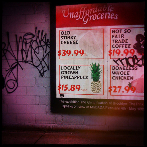thecandidcity:  gentrification of brooklyn billboard on Flickr.This billboard on Fulton Street was part of the promotion for the Museum of Contemporary African Diaspora Arts' (MoCADA) exhibition on The Gentrification of Brooklyn. These billboards were created by the Toronto based artists, Specter. The exhibition included the works of several Brooklyn-based artists, as well as those who have been forced to relocate as a result of gentrification.  Growing up in New York City, I've always been fascinated by the constant changes of neighborhoods. Whether it's gentrification or migration, everything evolves. Lately, it seems that in the never ending quest for cheap rents in Manhattan and now Brooklyn, the lower classes that have settled and made homes in these now desirable areas are being pushed out. First, it may start with a simple organic grocery, and then the real estate developers come, driving out established residents with their bulldozers.