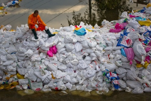 A monk sits atop a sandbag-fortified flood gate at Khlong Rapi Pat in Khlong Luang on the outskirts of Bangkok, Thailand. Thailand's worst flooding in decades is encroaching on Bangkok. (Photo by Daniel Berehulak /Getty Images)