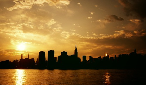 "Sunset over the New York City skyline as viewed from the East River.   In the last minutes before the night rides across the sky with its trailing blanket of darkness, the sun melts over the rapidly darkening silhouettes in the distance pouring itself into the water like liquid gold.   It's in these last minutes before the city lights illuminate the urban landscape like constellations, before every last ember of daylight fades that the remains of the day extinguish themselves in the long sighs of evening wanderers.  —-  View this photo larger and on black on my Google Plus page  —-   Buy ""Sunset Over The New York City Skyline"" Posters and Prints here, View my store, email me, ask for help, or subscribe to the mailing list."