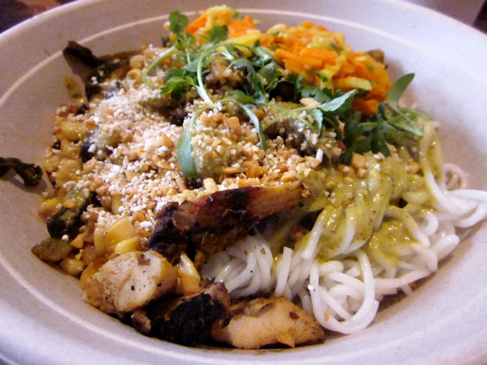 "Chicken Bowl at ShopHouse in Washington, DC Rice Noodles topped with Grilled Chicken, spicy Charred Corn, Mild Curry, pickled Vegetables, Herbs (Cilantro, Mint, Thai Basil), and crispy Rice, Garlic, and Peanuts On this quick low-key trip to The District, I was most excited for this meal. Why? ShopHouse is Chipotle's Asian spinoff whose name comes from the buildings (or row of buildings) that have restaurants in the bottom floor and living quarters up top. ""Asia's version of fast food."" I was impressed. It was really good. Not the portions of its big brother yet; but I was still full after it all. The chicken was great, the spicy corn was the best thing in the bowl, and the sauces and garnishes all added something. I just wish I got the spicier curry. Small misstep. Oh, and the noodles. They were cold - but apparently that's on purpose. Haven't caught on to that one yet. Maybe it'll grow on me. Will it be the next big thing? It's hard to say. I mean, I doubt it. Americans are a lot less familiar/comfortable with Southeast Asian food right now than they were with Mexican before Chipotle arrived about 10 years ago. However, I could definitely see Steve Ells propping a few of these up in the major cities. It's not like he needs to make a ton of money with these; he's already made enough for 10 or 12 lifetimes on the backs of overstuffed burritos and amazing guacamole. But we'll see. I hope I'm wrong."