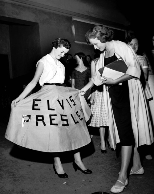 A fan shows off her dress at Elvis Presley's concert at Ellis Auditorium on May 15, 1956