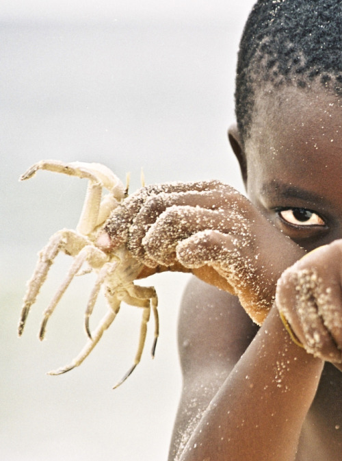 kilele:  Boy playing with a crab in Nigeria (exact location not given) Photo by Alejandra Ramirez Martin del Campo
