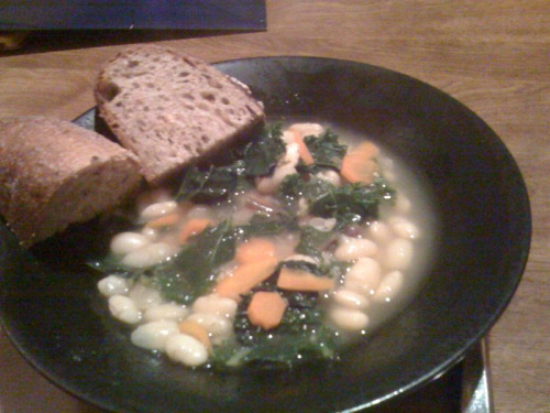 As it gets colder outside, this white bean and kale soup will warm you up.  Liz made it last night, and it was delicious!    Kale and White Bean Soup  (From Gourmet, via Epicurious)   1 lb dried white beans such as Great Northern, cannellini, or navy 2 onions, coarsely chopped 2 tablespoons olive oil 4 garlic cloves, finely chopped 5 cups chicken broth 2 qt water 1 (3- by 2-inch) piece Parmigiano-Reggiano rind 2 teaspoons salt 1/2 teaspoon black pepper 1 bay leaf (not California) 1 teaspoon finely chopped fresh rosemary 1 lb smoked sausage such as kielbasa (optional), sliced crosswise 1/4 inch thick 8 carrots, halved lengthwise and cut crosswise into 1/2-inch pieces 1 lb kale (preferably lacinato), stems and center ribs discarded and leaves coarsely chopped  Cover beans with water by 2 inches in a pot and bring to a boil. Remove from heat and let stand, uncovered, 1 hour. Drain beans in a colander and rinse. Cook onions in oil in an 8-quart pot over moderately low heat, stirring occasionally, until softened, 4 to 5 minutes. Add garlic and cook, stirring, 1 minute. Add beans, broth, 1 quart water, cheese rind, salt, pepper, bay leaf, and rosemary and simmer, uncovered, until beans are just tender, about 50 minutes. While soup is simmering, brown sausage (if using) in batches in a heavy skillet over moderate heat, turning, then transfer to paper towels to drain. Stir carrots into soup and simmer 5 minutes. Stir in kale, sausage, and remaining quart water and simmer, uncovered, stirring occasionally, until kale is tender, 12 to 15 minutes. Season soup with salt and pepper. Cooks'notes: •Soup is best if made 1 or 2 days ahead. Cool completely, uncovered, then chill, covered. Thin with water if necessary. Read More http://www.epicurious.com/recipes/food/views/Kale-and-White-Bean-Soup-106153#ixzz1bu3gElit