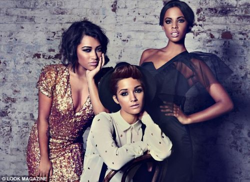 Frankie Sandford (M) of The Saturdays takes on the masculine role alongside Vanessa White (L) and Rochelle Wiseman (R), both also apart of the British and Irish pop, R&B and electropop girl group based in London, United Kingdom - The Saturdays. Frankie sits backwards on a chair in her shirt and braces, while Vanessa and Rochelle stand by her side in full eveningwear.
