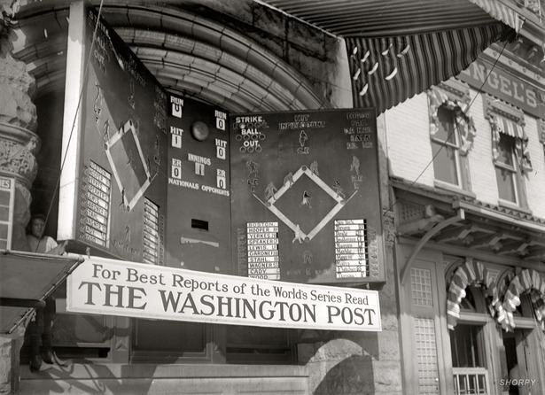 Amazing article at The Atlantic on how baseball games were shown to large crowds using manual displays, lights and puppets. The modern ESPN online gamecasts are very similar to how the games were shown to crowds back in the early 1900s.  There, a series of lights shone through the thin fabric indicate the progress and location of hits, base runners and fielders. At right in the photo are ball, strike, and out lights. This was not a one man job. Several controlled the indicators, one acted as announcer.