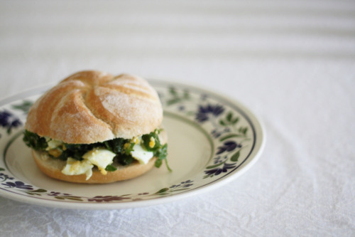 qualityrecipes:  Healthy Egg Salad Sandwich 2 slices organic wholemeal bread, pita bread or crusty roll, toasted, untoasted; buttered or not, whichever is your preference1 just hard boiled free range egg1 tspn Dijon mustard1 tspn extra virgin olive oil1 tblspn each finely diced green parts of spring onion, fresh continental parsley and basilHandful salad greens (I use mixed gourmet salad leaves, baby spinach, rocket, whatever's available and nice)Cracked black pepper and sea salt Mash egg roughly with a fork; then mix in the mustard, oil and herbs, adding seasoning if desired.  Place filling in between bread with salad. Serves: 1