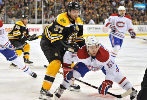 Patrice Bergeron watches the loose puck against David Desharnais of the Montreal Canadiens.