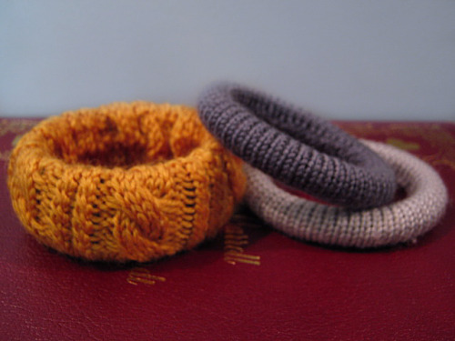 Would you get a load of these knit bangles? These have to be the cutest bracelets I've ever seen! It cost $0.50 for all three at my favorite little charity thrift shop. The big yellowy one still had its original tag on it, and it cost $7.50 at Old Navy! What a fantastic deal!  I love bangles, but I usually don't wear them much because it bothers me when they're constantly slamming into my hands whenever I lower my arms. The soft knitting makes that a non-issue! I absolutely adore these colors too, so I think these bracelets might have been designed specifically for me.  If you like them and know how to knit around things, you could probably make some like this for yourself! Just pick up an unloved bangle for a quarter or two at a thrift shop, pick out the perfect yarn, and you're good to go! If you don't know how to knit but you're handy with a glue gun, you could probably achieve a similar effect by wrapping the yarn around it in tidy lines. The bangle underneath these is a light black so that if any of it shows between the stitches it just looks like a shadow. It probably wouldn't be a bad idea to hit any bangle you plan on knitting over with a quick coat of light black spray paint, especially if the bangle's a bright color and/or you're using a dark yarn, Be sure to use a spray paint appropriate for the material your bangle is made out of.