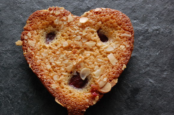 Makes 12 heart shaped financiers/friands175g unsalted butter3 whole star anise175g demerara sugar175g ground almonds, plus extra for dusting moulds6 large egg whites, (about 180 g)Pinch of salt1 teaspoon microplaned orange zest36 - 48 small, frozen raspberries36 white chocolate chips1/3 cup flaked almonds, roughly crushed by hand  MAKE THE BEURE NOISETTE: Put the butter in a small saucepan. Let it melt and then bring it to the boil over medium heat, swirling the pan occasionally. As it boils the top will become foamy. Continue to cook the butter until it looks clear and the milk solids have dropped to the bottom of the pan and have turned deep brown. The butter should smell nutty. Remove from heat and immediately pour through a cheesecloth-lined strainer. Add 1 star anise to the strained warm butter and allow to cool to room temperature. Make a powder of the other 2 star anise by blending in a spice grinder. Set aside.   TOAST THE FLOUR: Place the almond flour (meal) on a baking sheet and bake for 6 - 8 minutes at 200 degrees C or until lightly browned. Remove from oven and let cool down.   MAKE THE BATTER: Make the batter by whisking the egg whites and a pinch of salt till the egg whites become a touch frothy. Remove 3 tablespoons of the browned butter (For greasing the pans) and add the rest with the almond flour, sugar and a pinch of ground star anise to the eggs. The batter will thick - don't worry. Allow to rest in the fridge for four hours or overnight. Note that you can refrigerate the batter for up to three days.   TO BAKE: Preheat the oven to 160 degrees centigrade. Then grease mini muffin tins, financier moulds or cookie tins with the beurre noisette or plain melted butter then dust with flour and tap out the excess.   Stir in the microplaned orange zest to the mixture along with the chocolate chips, whisking well to combine. Fill the moulds with the batter about 3/4s full as the cakes will rise. Stud with 3-4 raspberries and sprinkle over the crushed flaked almonds over the top.   Bake in the centre of the oven for 12 - 14 minutes or till the friands/financiers are golden, puffed up, springy to the touch with slightly crusty edges. They should still feel a touch soft.   Allow them to stand for a few minutes once out of the oven. Loosen the edges and bottom with a rubber knife or small spatula and then remove to a rack to cool completely. The bottoms have a tendency to be a bit sticky when still warm, so you may want to put them upside down on the rack, or put them on a sheet of parchment paper.   Enjoy with a nice cup of mint tea! Or coffee. ASK THE HOTLINE ABOUT THIS STEP!  Variations: Cherries; Chocolate, with the addition of cocoa powder, Matcha (green tea), Chopped nuts and dried fruit……And on and on and on.