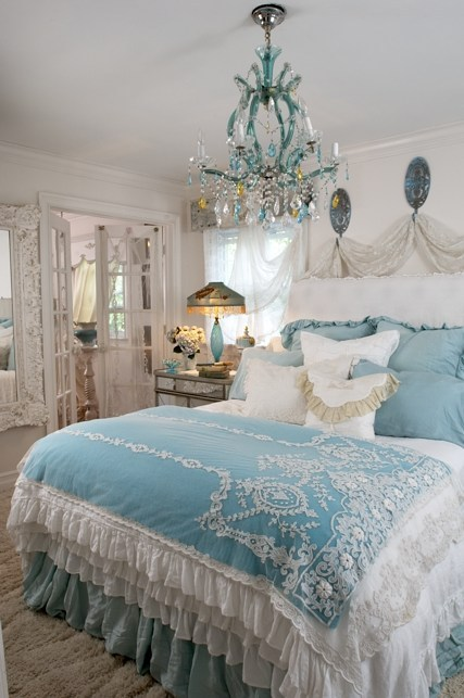 Pure romance. Bedspread with lace appliques, tons of ruffles, a mound of cushions, and a delightful aqua and clear crystal chandelier are some of the highlghts of this Shabby Cottage Chic bedroom (via shabby cottage,)