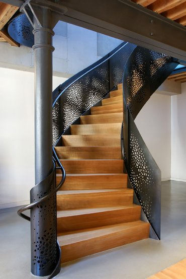 This is a fascinating staircase. In place of railings is a solid sheet of metal that is intricately pierced for a lacy look of light and shadow… the dark color also beautifully sets off the varnished wood steps. Plus I love how the metal sheeting and handrail wrap sinuously around the support pillar at the foot of the stairs. Industrial, but elegant… would look marvelous in a loft.