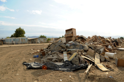Rotting and disassembled trailers and other refuse are regularly dumped at the edge of the Lawson Mobile Home Park in Coachella, California. Read more about this area in our story On edge of paradise, Coachella workers live in grim conditions. Photo by Carlos Puma.