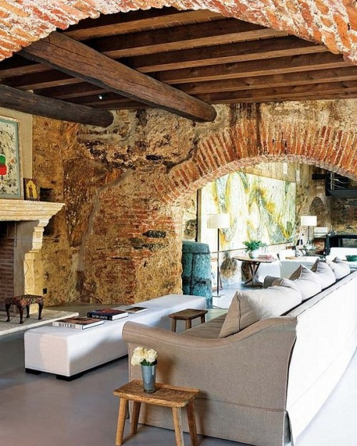 Fantastic… brick walls and arches in a living room in a converted home with a fascinating history. Located in Western Spain, this home was previously an old oil mill, and was originally constructed by monks in the 12th century.