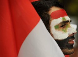 London - A protester, with his face painted in the #Syrian's flag colours, in a demonstration against #Assad outside the Syrian embassy. (AFP Photo/Ben Stansall)