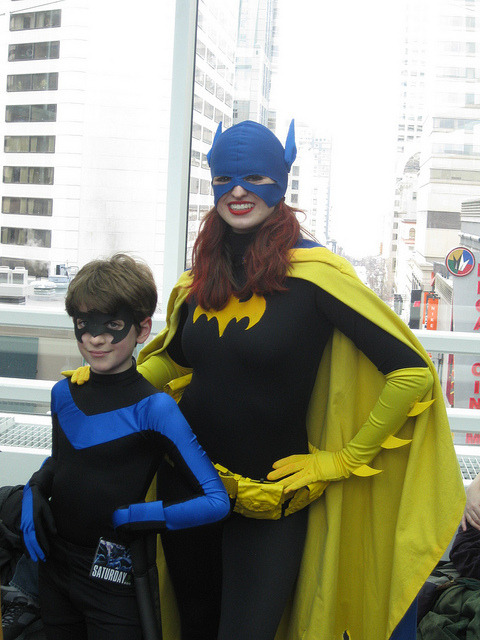 cosplayingchildren:  [Description: An adult Batgirl/Barbara Gordon poses with a young black and blue costumed Nightwing. I don't see many Nightwing costumes, and definitely not on little kids, and thus this makes me brilliantly happy!]