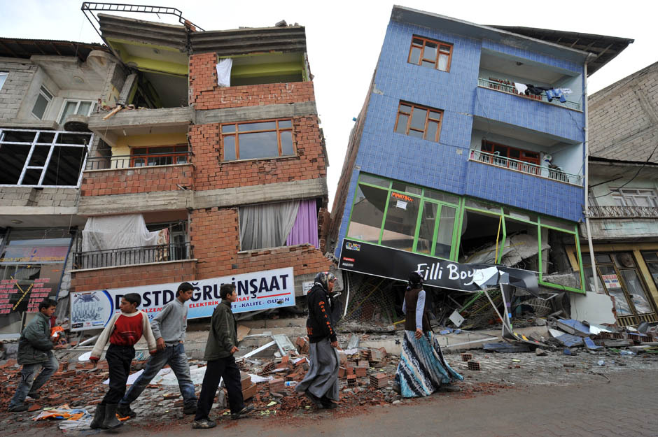 People walk in front of collapsed buildings after an earthquake in Ercis, province of Van, on October 26, 2011. Homeless survivors of Turkey's devastating earthquake shivered in sub-zero temperatures on Wednesday as the government admitted that it was struggling to cope with the demand for shelter. [Credit : Mustafa Ozer/AFP/Getty]