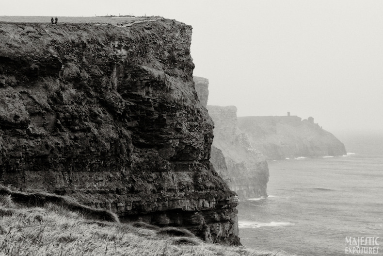 Walking the Cliffs by Benjamin Padgett  A couple takes a stroll along the top of the Cliffs of Moher in County Clare, Ireland.   The cliffs rise as much as 702' (214m) above the Atlantic Ocean while stretching over 5 miles (8km). Read more about the Cliffs on IRElogue!