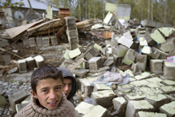 Guvecli, Turkey. Two boys stand in front of the rubble of a building that collapsed in the recent earthquake. [Credit : Morteza Nikoubazl/Reuters]