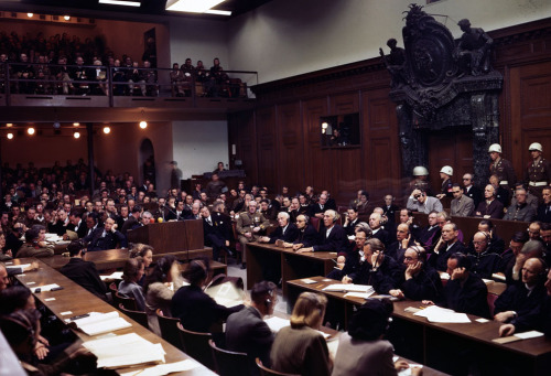 The interior of the courtroom of the Nuremberg War Crimes Trials in 1946 during the Trial of the Major War Criminals, prosecuting 24 government and civilian leaders of Nazi Germany. Visible here is Hermann Goering, former leader of the Luftwaffe, seated in the box at center right, wearing a gray jacket, headphones, and dark glasses. Next to him sits Rudolf Hess, former Deputy Fuhrer of Germany, then Joachim von Ribbentrop, former Nazi Minister of Foreign Affairs, Wilhelm Keitel, former leader of Germany's Supreme Command (blurry face), and Ernst Kaltenbrunner, the highest ranking surviving SS-leader. Goering, von Ribbentrop, Keitel, and Kaltenbrunner were sentenced to death by hanging along with 8 others — Goering committed suicide the night before the execution. Hess was sentenced to life imprisonment, which he served at Spandau Prison, Berlin, where he died in 1987. (AP Photo/STF) #