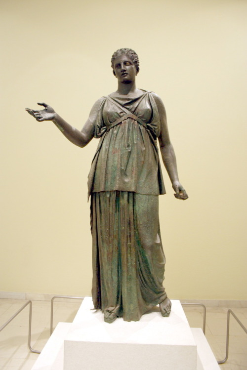A bronze statue of Artemis wearing a chiton and a bust support with one strap crossing her chest, ca 100 BC