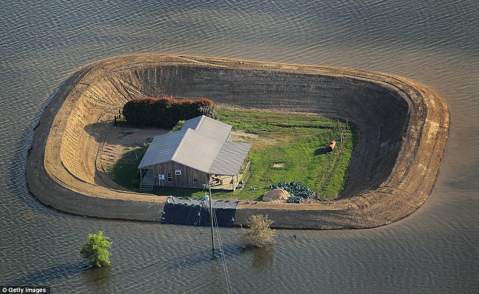 Aerial photos of houses along the flooded Mississipi (2011). The house has no views of the landscape because the flood walls are as high as the roof. A strange world we live in.