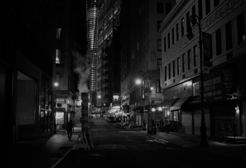 "Night and shadows in Lower Manhattan. Financial District, New York City  At night after the multitudes have retreated to their homes away from the buildings and streets that hold them close during the day the city relaxes shaking the dust of the long day from its concrete limbs.  The street lights flicker like dream-heavy blinks of an eye while smokestacks exhale world-weary breaths of smoke into the yawning night air.  —  This is a re-post from a few months ago. There was a mishap over at my Google Plus account which resulted in my post there being eaten up so I am re-posting to re-add the post plus the writing to my main album there.   —-  View this photo larger and on black on my Google Plus page  —-  Buy ""When Night Falls"" Posters and Prints here, View my store, email me, ask for help, or subscribe to the mailing list."
