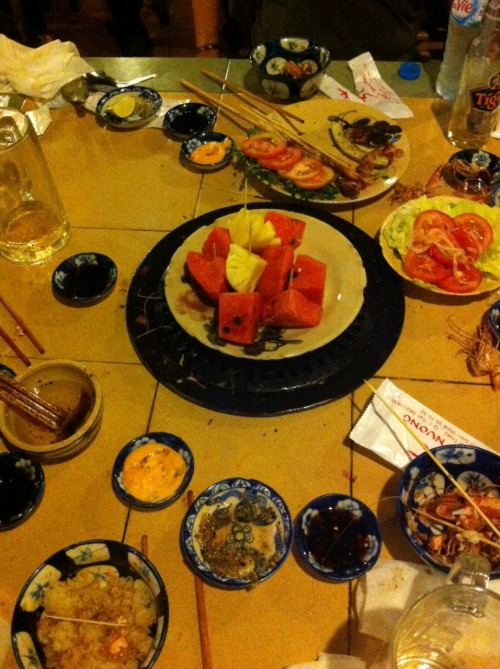 The remnants of our meal last night at 3T Quan Nuong, a Vietnamese barbecue place on the roof of Temple Club, the restaurant that literally every tourist guide to Ho Chi Minh City will recommend you try. Skip the more formal Temple, and eat outside, in the smoke from the grills scattered at picnic tables, in the light cast by paper lanterns, and if there's a birthday, the sparklers that pop in the darkness. Beef with lemongrass and chili. Wild boar with five spices. Barbecue filets of fish. Prawn with lime and salt. Okra and eggplant. Garlic fried rice. Spring rolls. Mugs of Tiger beer. And for the swan song, huge fresh chunks of pineapple and watermelon.