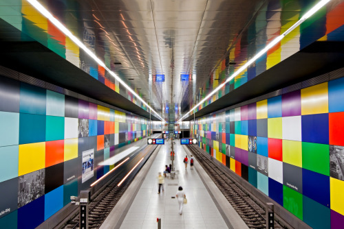 "thephotochain:  U-Bahn Station Georg-Brauchle Ring - Line U1 The Munich U-Bahn (German: U-Bahn München) system is an electric rail rapid transit network in Munich, Germany. ""U-Bahn"" is the German contraction for Untergrundbahn or ""subway"". Today the U1 has a length of 12.2 km. It starts at Olympia-Einkaufszentrum. On the way south it follows Hanauer Straße to Georg-Brauchle-Ring, which has been designed by Franz Ackermann, reaching Westfriedhof. It continues via Gern to Rotkreuzplatz. Below the Nympenburger Straße it goes on to Maillingerstraße and Stiglmaierplatz and finally merges into the U2 track at München Hauptbahnhof. Fraunhoferstraße, the next station, is also reached in separate tunnels, which had to be excavated using tunneling shields due to the proximity of the River Isar. However, the two tubes are connected by the platform, which demanded large pillars that are characteristic for this station. The next station, Kolumbusplatz, is a junction which has three tracks. Here U1 branches off U2 again. The southbound branch line was opened in 1997 and traverses the colourful station Candidplatz, eventually reaching Wettersteinplatz. The following station, St.-Quirin-Platz has an extraordinary architecture as it is covered by a large, shell-like structure made from glass and steel, which is drawn nearly down to track level on one side. Below Neupliastraße, there is the terminus of U1, Mangfallplatz. - Wikipedia"