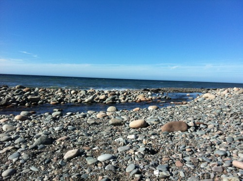 Rock beach.  Stream running to the Atlantic Ocean from the mountains.