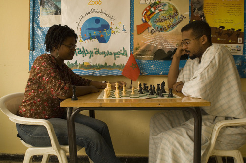 A Peace Corps Volunteer plays chess with a member of her community.
