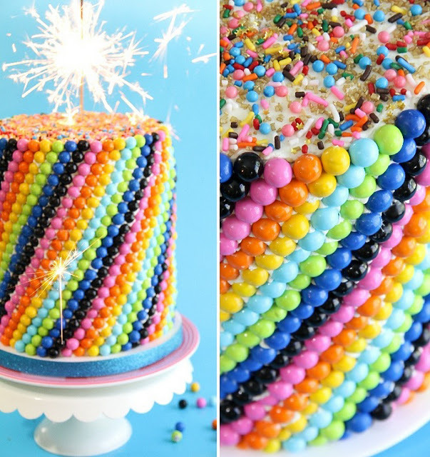 "gossipchef:  The Sprinkle Bakes Sixlets CakeCake:2 boxes white cake mix2 cups all-purpose flour2 cups granulated sugar1 ½ tsp salt2 2/3 cups water1/4 cup vegetable oil 2 tsp real vanilla2 tsp almond extract2 cups (16 oz) sour cream8 large egg whites ½ tsp Wilton sky blue food coloring¾ cup multicolored jimmies (the kind you find in the ice cream section of the grocery store will hold up well in the batter)2 lbs. Sixlets candiesVarious and sundry sprinkles of your choosing for the top of the cake Preheat oven to 325 degrees.  Grease five 7-inch cake pans and line with parchment.  You may also choose to use four 9"" cake pans. Place all dry ingredients in a large mixing bowl and stir together with a wire whisk. Add the remaining ingredients and beat on a low speed for 2 minutes until smooth.  Remove 6 cups of batter and tint with the sky blue food coloring.  Add the multicolored jimmies to the blue batter and fold gently to combine.  Pour batter in pans, alternating blue and white batters.  Pull a knife or skewer through the batter to create a swirl.  Bake cakes for 40 -50 minutes, or until cake springs back when pressed in the middle. Icing:8 egg whites1 cup sugarPinch of salt32 tbsp. (1 lb. or 4 US sticks) unsalted butter, cubed2 tsp. clear vanilla extractSet a saucepan filled 1/3 full of water over medium high heat and bring to a simmer. Whisk together egg whites, sugar and salt in a heat-proof bowl.  Set over simmering water and whisk until mixture is hot and sugar has dissolved. Transfer to the bowl of a stand mixer fitted with the whisk attachment. Beat on low speed for 2 minutes, then increasing to medium-high until stiff peaks are formed. Continue beating at medium-high speed until mixture is fluffy and has cooled. Remove whisk attachment and replace with paddle attachment Decrease mixer speed and add butter, a little at a time, beating until well incorporated before the next addition. Add vanilla extract. Beat until icing is smooth.  Increase speed if icing is slow to firm. AssemblyIcecakes and stack them, making sure the edges are as even as possible.  Apply an even coating of icing to the outside of the stacked cakes using an off-set spatula, filling any gaps and crevices. Starting at the bottom of the cake, gently push sixlets into the icing. Create a line of alternating colors (or use a solid color, your choice!)  To achieve the graduated swirl, use colors in the same order on the second line, but move the first color over one space to the right.  Continue this pattern all the way up the cake.  By the time you're done, (about  1 hour 20 minutes) you'll be in a hypnotic state from applying sixlets sprinkles.  This process is very meditative – enjoy the zen! Sprinkle the top of the cake with various and sundry.  Add a sparkler if you're into pyrotechnics…which I certainly am!"