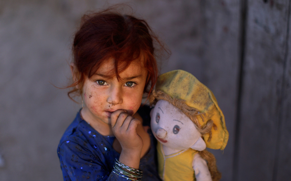 Three-year-old Afghan refugee Nageen Jihandad plays with her doll in a slum near Islamabad, Pakistan