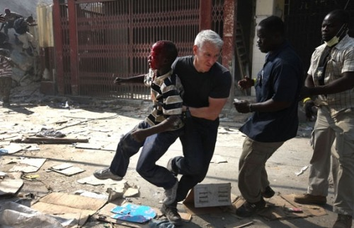 Anderson Cooper saving a boy in Haiti during a shooting. A slab of concrete was dropped of the boys head.