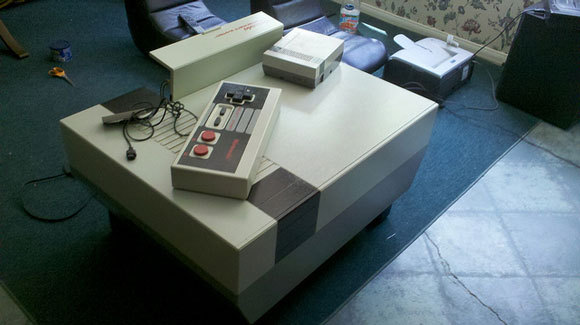 NINTENDO ENTERTAINMENT SYSTEM : COFFEE TABLE  We've seen some superb retro projects before with the Giant NES Controller and DIY Pinball Coffee Table, but this Nintendo Entertainment System (NES) coffee table really raises the bar.  The giant version of the original is not just for looks – the NES coffee table's front cover has a fully functional jumbo sized NES controller for playing old 8-bit video games.   Source: http://hacknmod.com/hack/geek-decor-nintendo-entertainment-system-coffee-table/
