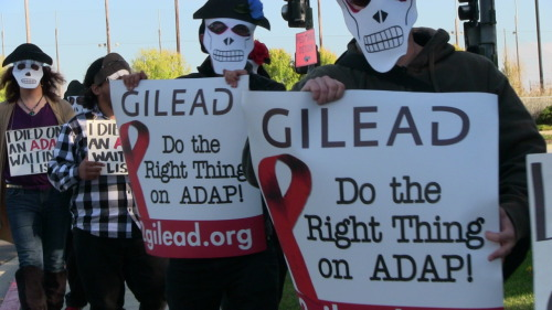 "By Christina McEwen AIDS advocates staged a ""Day of the Dead"" protest yesterday in Foster City, California in front of the headquarters of drug company Gilead Sciences Inc. The ""Day of the Dead"" mock funeral theme was designed to honor Americans who have died while on AIDS Drug Assistance Program (ADAP) waiting lists.  More than 6,500 Americans are now on waiting lists to receive lifesaving AIDS drugs through these state programs.  The waiting lists have been created largely because programs cannot afford to care for as many low-income Americans since the price of AIDS drugs has skyrocketed.  The price of Gilead's key AIDS drug Atripla is more than $10,000 per patient per year, for example. The group was asking Gilead to lower AIDS drug prices for state programs NOW!"