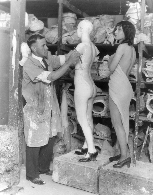 memoriastoica:  A carver sculpts a mannequin after the likeness of the model standing in front of him.