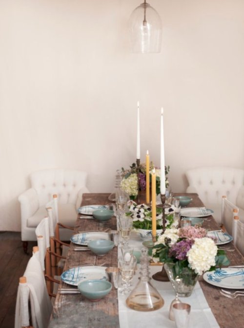 A simple dining space is elegantly dressed for a dinner with a tablescape loaded with flowers, pottery dinnerware, and vintage accents (via apartment 34: On My Easter Menu)