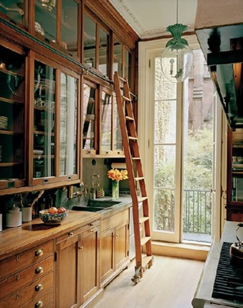 Aged oak cabinets and tall, stacked glass-fronted cupboards, reached by a sliding library ladder, give this narrow kitchen both great appeal and tons of storage space (via Little Green Notebook: GIVE AWAY: Restoring a House in the City)