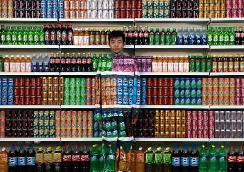"photo credit:  AP National Geographic: Life imitates store shelves as artfully attired Chinese artist Liu Bolin blends into a display of soft drinks at his Beijing studio August 10. Assistants later painted him to complete the illusion. Entitled ""Plasticizer,"" the piece is intended to express Bolin's speechlessness at the discovery of plasticizer contamination in food products, according to the Associated Press. Plasticizers are additives normally used to make plastic and other nonfood products more pliable.  (via Pictures We Love: Best of August)"