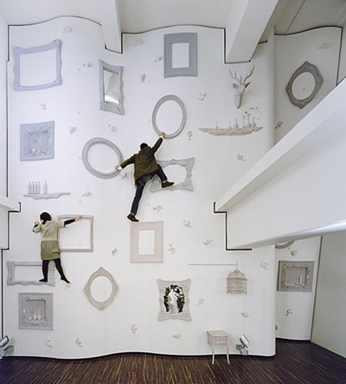 Alice in Wonderland Climbing Wall by Nendo Located in the Omotesando shopping center in Japan, this fashionable  rock-climbing wall contains baroque picture frames, mirrors, deer heads,  birdcages, and flower vases as grasping points so you can feel  pretentious while you work out. http://www.nendo.jp/en/
