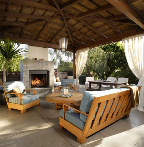 Outdoor living and dining room combo with a fireplace and privacy curtains in Southern California (by joyoendho)